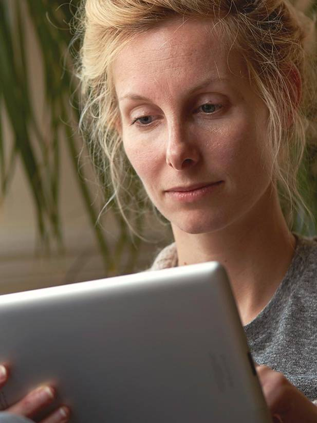 Woman fills out an online medical history form at home for her visit to the doctor.