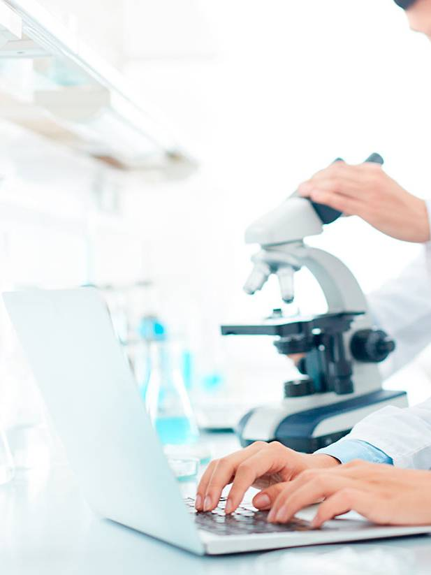 Laboratory assistants work on a laptop and a microscope on order entry.